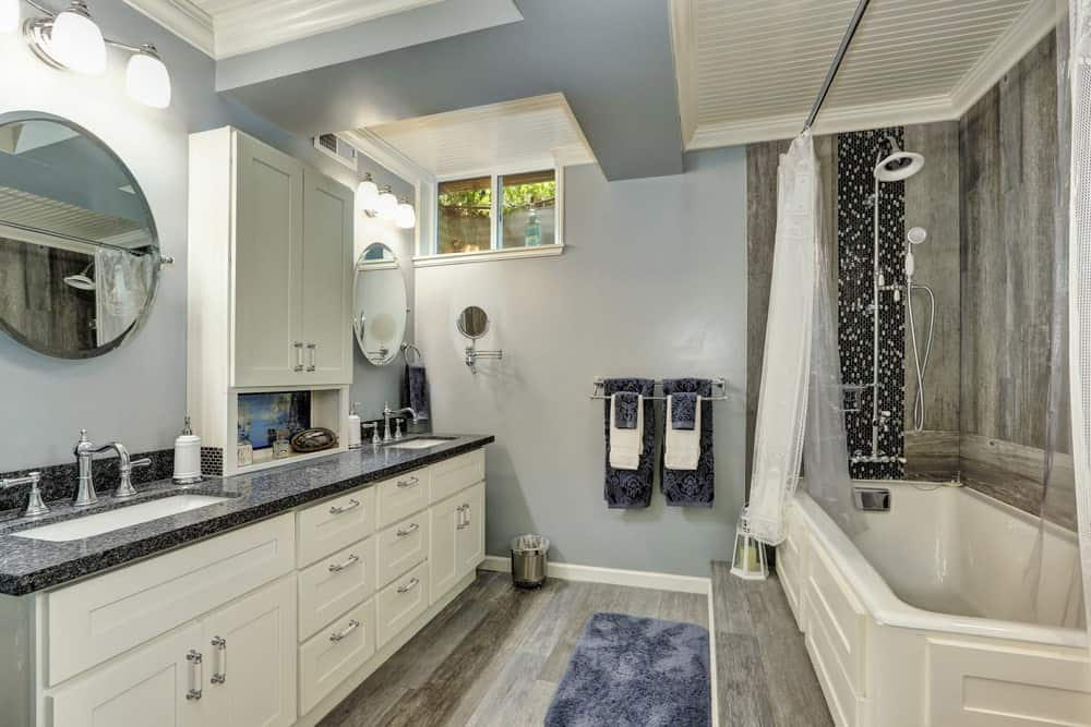 Classic blue bathroom with a rustic tone from the hardwood flooring and walls by the shower and tub area covered in transparent curtain.