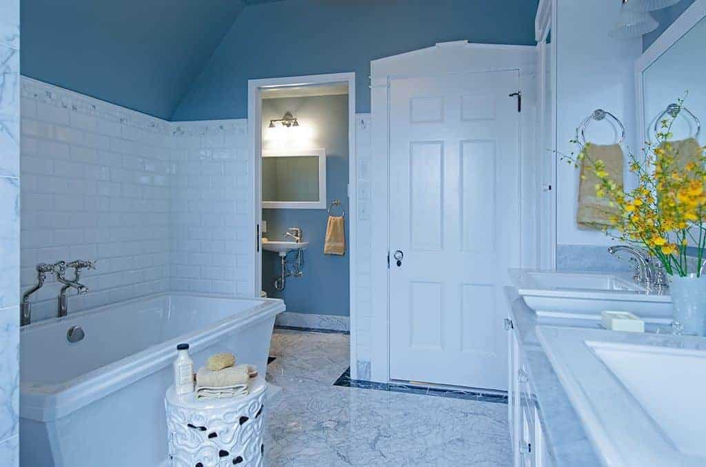 A white ornate stool sits next to the freestanding tub in this blue bathroom offering a toilet area and dual sink vanity accented with a lovely potted flower.