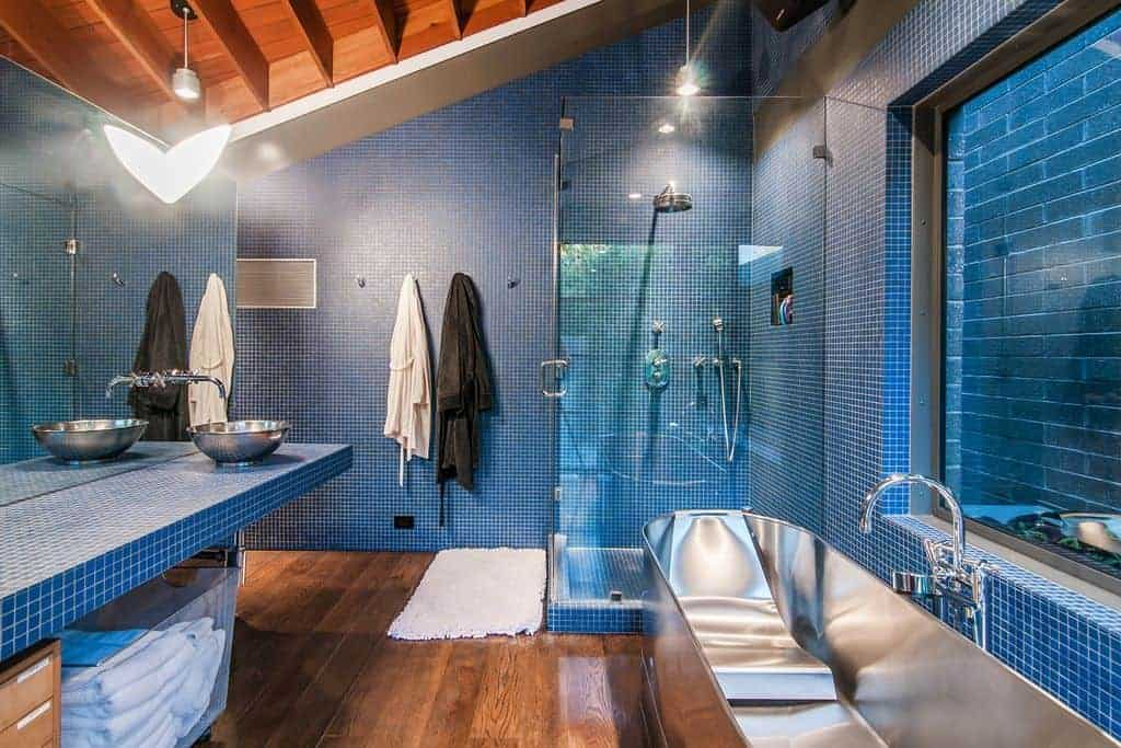 Cozy bathroom features blue tiled walls and countertop along with wood beam ceiling that complements with the hardwood flooring topped by a white shaggy rug. It includes a stainless steel bathtub paired with a gooseneck faucet.