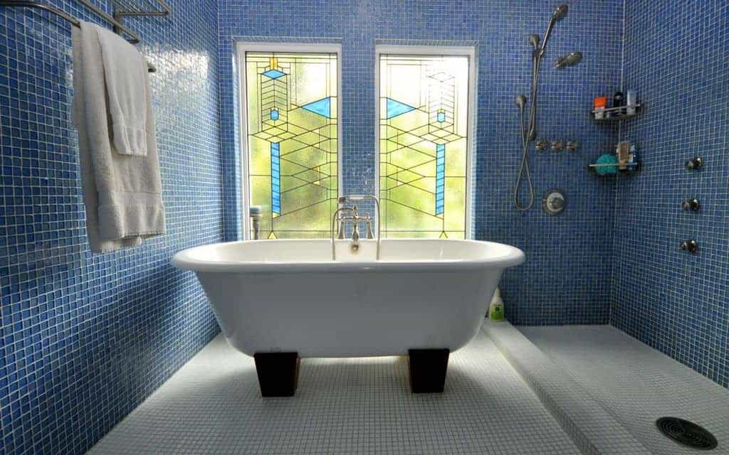 Charming bathroom with an open shower area and a pedestal tub surrounded by fabulous stained glass windows and blue tiled walls that are fitted with chrome fixtures and corner shelves.