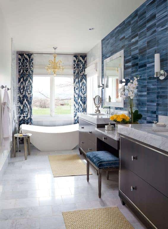 Classy bathroom illuminated by a gold chandelier that hung over a freestanding tub along with natural light that flows through the picture windows covered in blue patterned drapes.