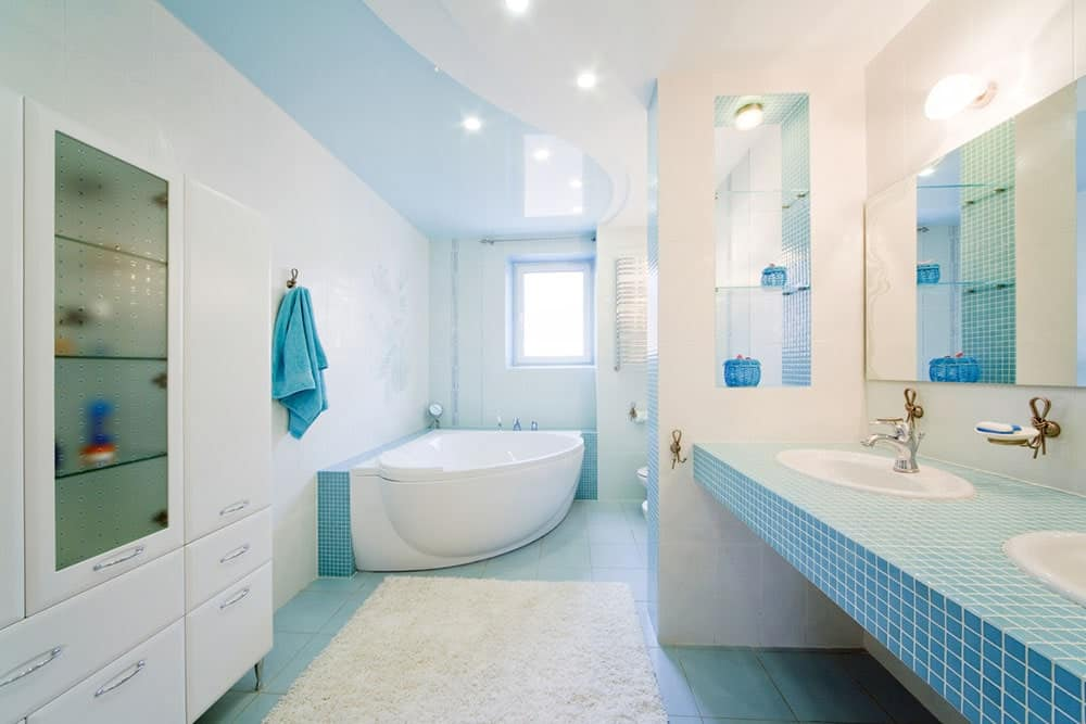 Bright bathroom boasts a drop-in bathtub and sleek white cabinet across the blue tiled countertop fitted with dual sink and chrome faucets.