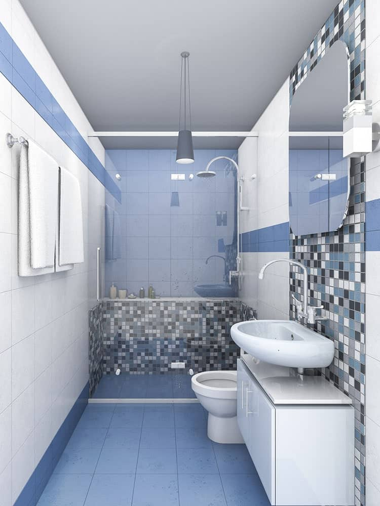 Spectacular mosaic tiles add a nice accent to this blue bathroom showcasing a walk-in shower and toilet next to the wall-mounted vessel sink with white storage underneath.