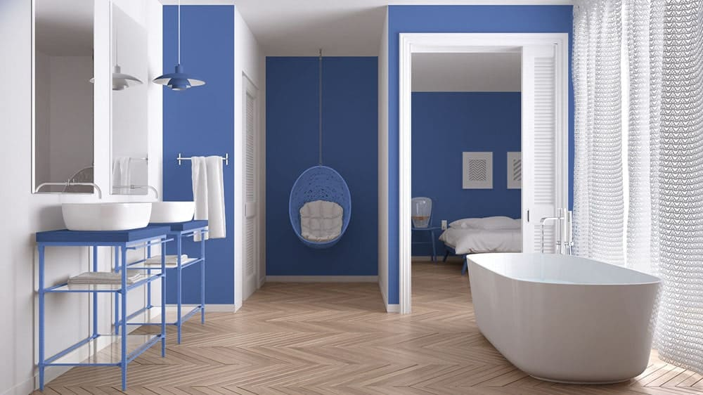 Blue bathroom features his and her vessel sink washstands along with a round hanging seat and a pedestal tub by the glazed window covered with knitted curtains. It has herringbone wood flooring and a white louvered slider that opens to the master bedroom.