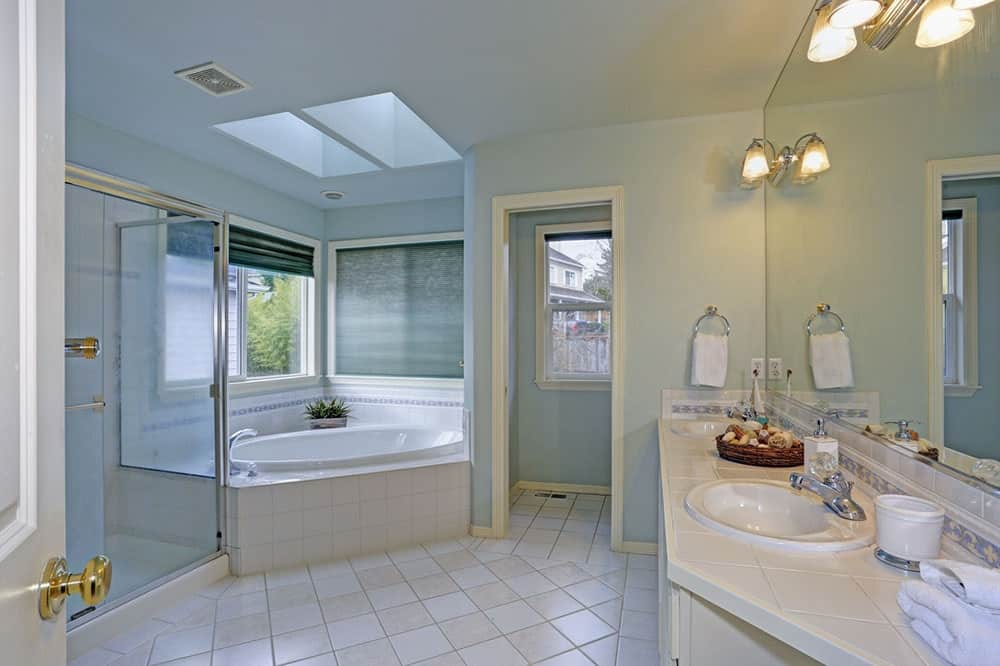 A walk-in shower sits next to the corner bathtub in this sky blue bathroom with a toilet area and white sink vanity lighted by chrome sconces.