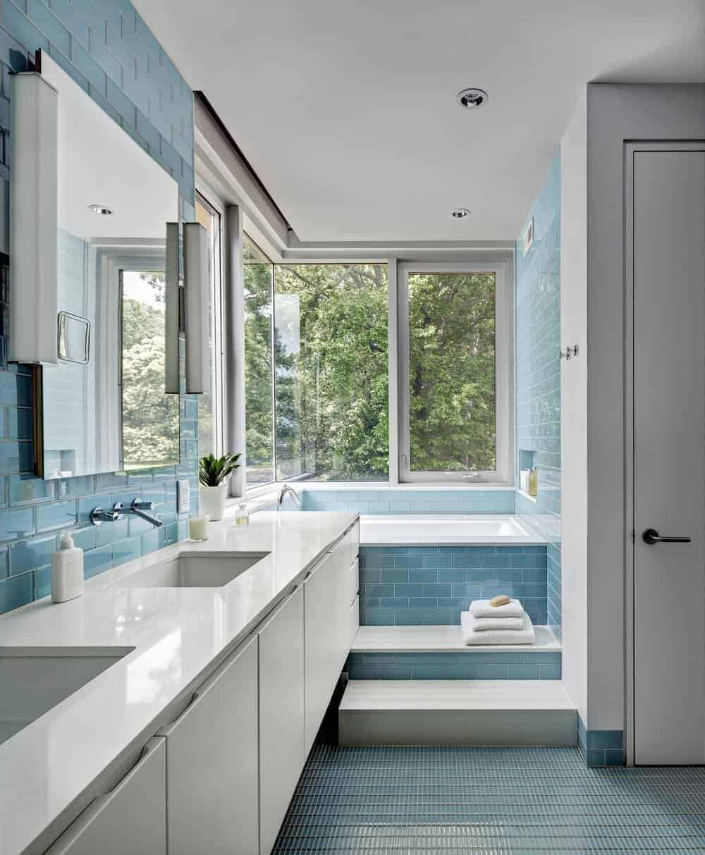 Light and airy bathroom with sleek white sink vanity and a deep soaking tub by the glazed window bringing plenty of natural light in.