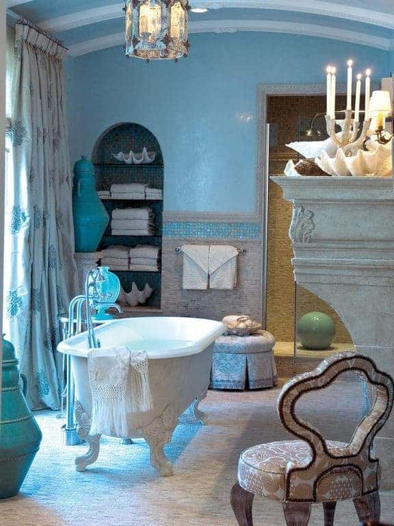 A charming cushioned chair faces the clawfoot bathtub lighted by a marvelous pendant in this blue bathroom showcasing a skirted ottoman and arched inset shelf filled with towels and shell bowls.