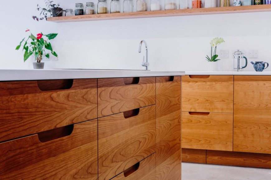 Cherry-veneered drawer fronts with scoop handles under the kitchen worktops.