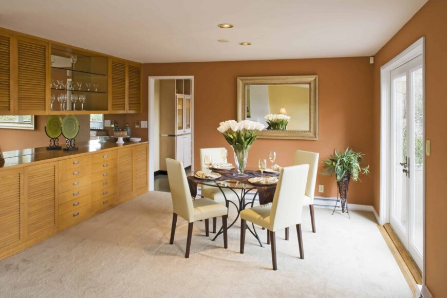 The brown walls of this bright dining room is bathed with natural lights that are coming from the bright glass doors that complements the round glass-top dining table surrounded by wooden chairs that have beige cushions over a carpeted flooring.