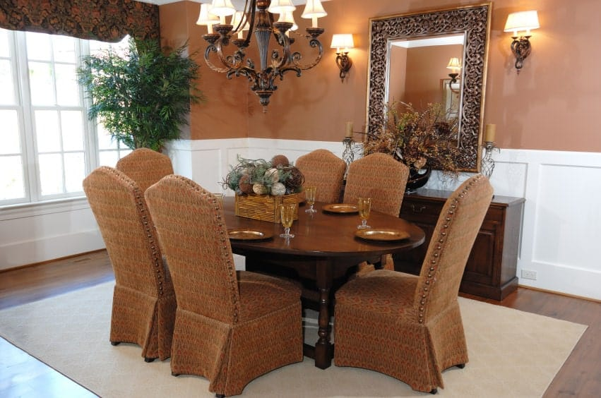 This is an elegant fusion of brown and white elements with the brown patterned chair slip covers matching with the brown upper walls that is contrasted by the wainscoting. There is also a brown wrought iron chandelier that matches the elliptical wooden table.
