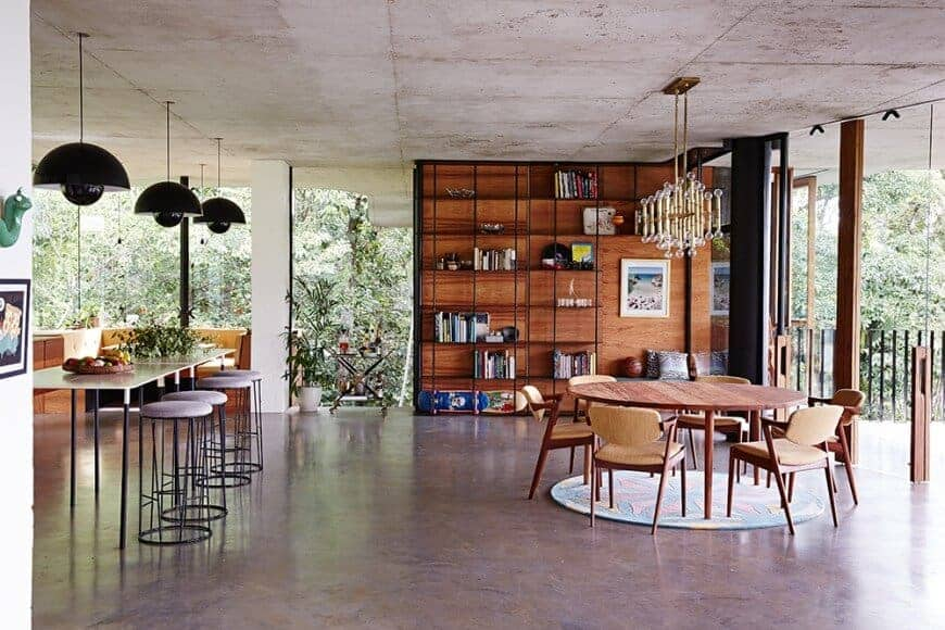 The beautiful lush greenery of the surrounding landscape is showcased by the glass walls brightening the industrial gray and brown flooring topped with a circular colorful area rug and a circular brown wooden table paired with wooden armchairs.