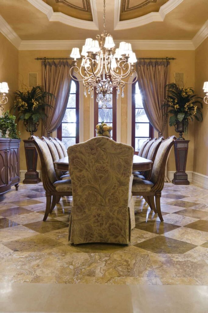 This dining room is filled with different shades of brown from its brown marble flooring, brown patterned slip covers for the dining chairs and the curtains and decors on the beige walls.