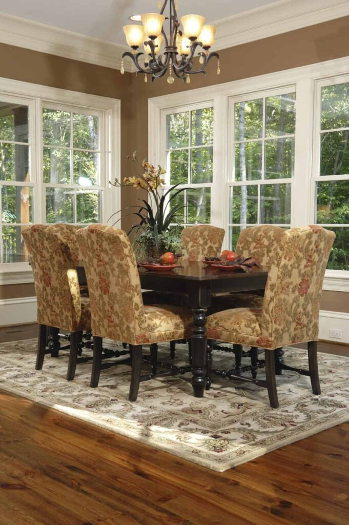 This chic dining room has brown floral patterned cushions on the dining chairs matching the floral patterned area rug that contrasts the hardwood flooring. It also contrasts the dark brown hue of the dining table brightened by the windows.
