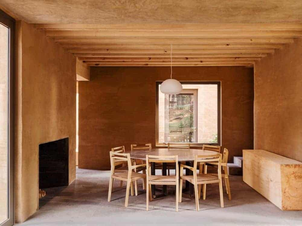 The bare wooden ceiling has exposed wooden beams that support a white modern pendant light over the circular wooden dining table that sits eight people on wooden chairs with rustic woven seats warmed by a fireplace on the bare wooden wall.