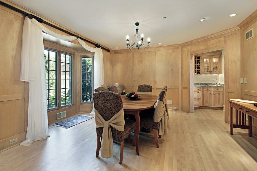 The wooden elliptical dining table is in the middle of this dining room that has bare wooden walls matching the flooring. This is illuminated by the natural lighting provided by the tall windows with white curtains.