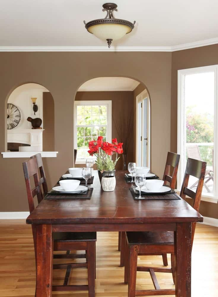 There is a lovely arched entryway that leads into this dining room matching the window beside it. These are lovely accents to the brown walls that are lined with contrasting white molding and white ceiling. This is paired with hardwood flooring that complements the redwood table and its wooden chairs.