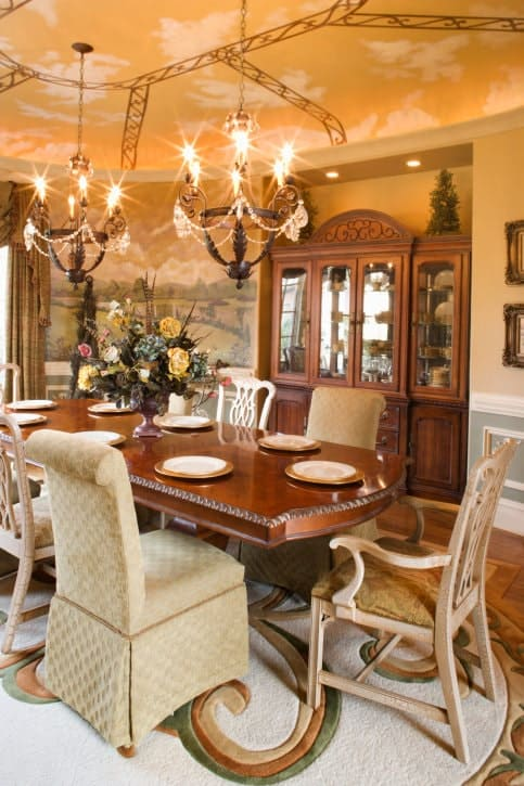 The amber-like hue of the ceiling that depicts a lovely sunset sky is augmented by the warm yellow lights of the two ornate chandeliers hanging above the large elegant brown wooden table. This pairs well with a dining room cabinet that is embedded into walls that are dominated by a wallpaper with depictions of a meadow.