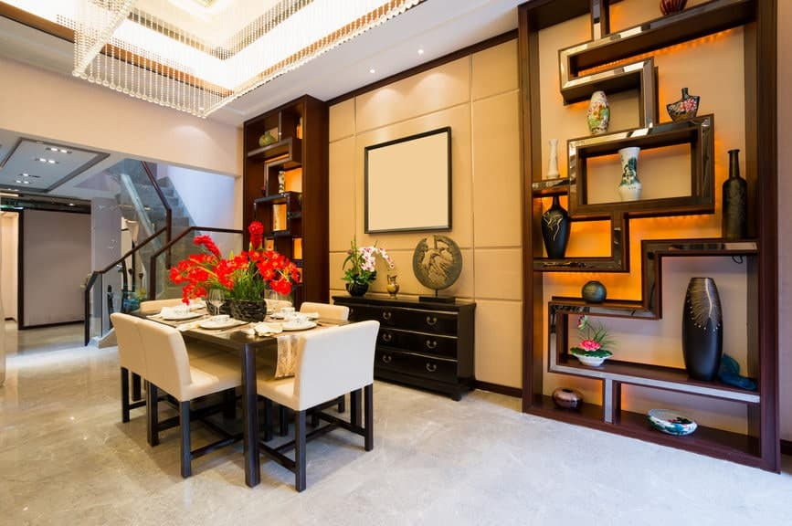 This elegant formal dining room has a bit of oriental flair to the design of its dark wooden shelves that showcase various pottery and decors. These two shelves are flanking a dining room cabinet that matches the dark wooden table paired with beige chairs.