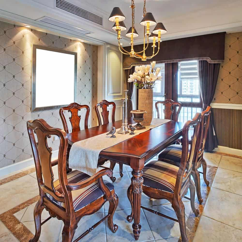 The dark wooden dining table has intricate and elegant pencil legs that pairs well with the elegance of the curved and carved chairs and their legs. This matches well with the light brown wallpaper and the dark brown curtains that has the same hue as the chandelier's hood.