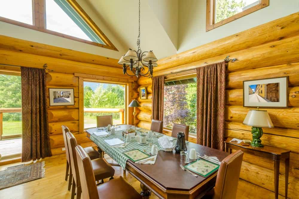 This is a charming dining room that balances elegance with warmth and homey. It has a log cabin finish to its walls that is complemented by transom windows and a high ceiling that supports a wrought iron chandelier hanging over the elegant wooden table and its leather-cushioned chairs.
