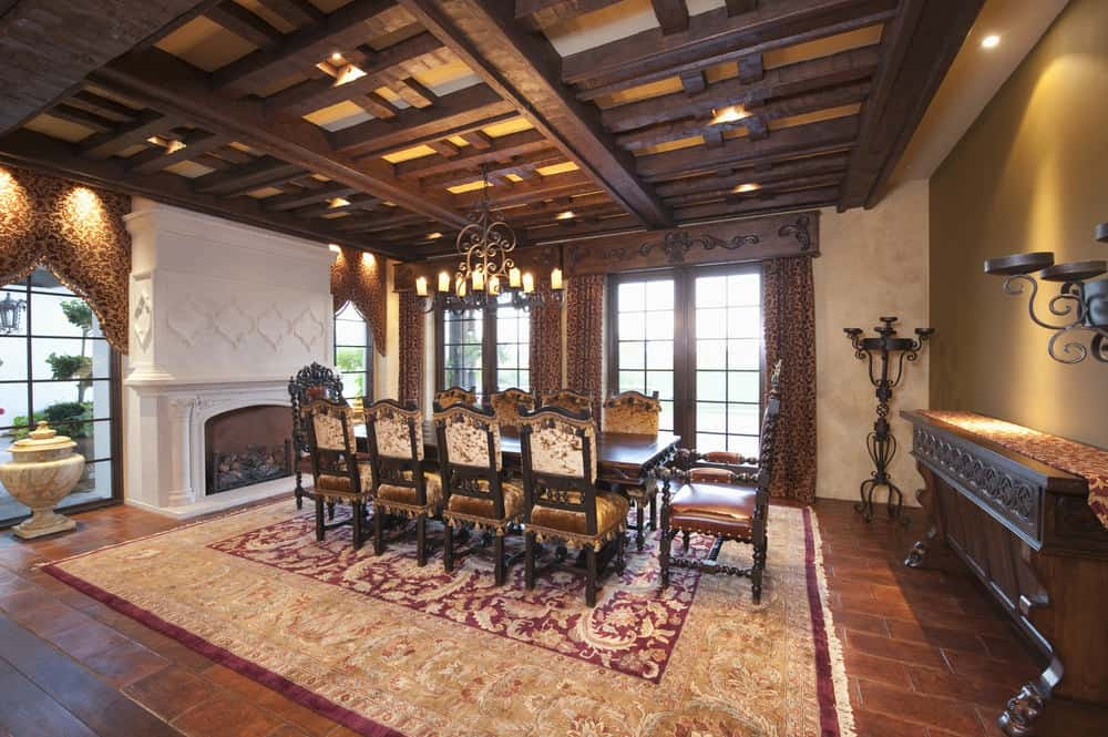 This elegant formal dining room is filled with rich earthy hues that augment the ceiling filled with dark wooden exposed beams, terracotta flooring tiles topped with a colorful intricate area rug and a wooden dining set. This makes the fireplace stand out with its white mantle.