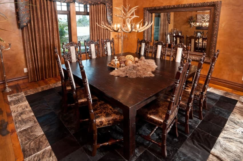 The rustic chandelier hanging over the wooden square table is made of deer antlers matched with an animal fur decoration on top of the table to complete the aesthetic. This is augmented by brown walls, brown curtains and a brown-framed mirror.
