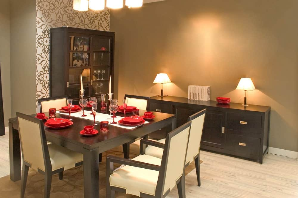 The red ceramic ware contrasts the dark brown wooden table that perfectly matches with the wooden dining chairs that has beige leather cushions. This also matches with the low dining room cabinet with a couple of table lamps against the gray wall.