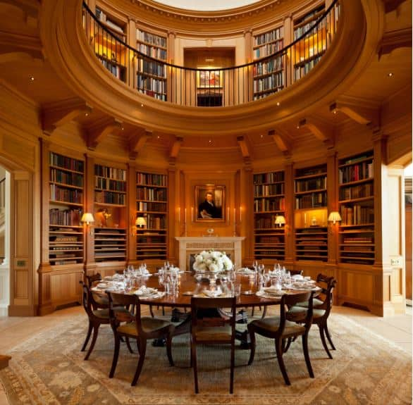 This unique dining room is within the wooden walls of a circular two-level library with its walls filled with bookshelves adorned with wall lamps and a fireplace by the large wooden circular table surrounded by wooden chairs on a light hued patterned area rug.