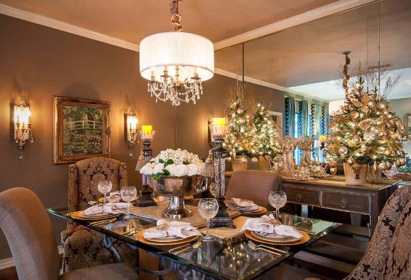 This elegant dining room is in full Christmas mode with its pair of table-top small Christmas trees on a console table that fits with the brown walls and brown cushioned dining chairs of the glass-top dining table lit with a small chandelier above.