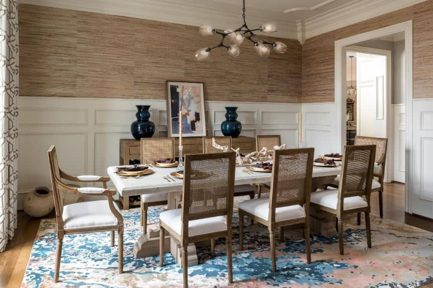 The simple brown walls, brown chairs and wooden dining table are given a nice colorful background with the addition of the beautiful area rug and the painting on the dining room cabinet that stands out against the wainscoting.