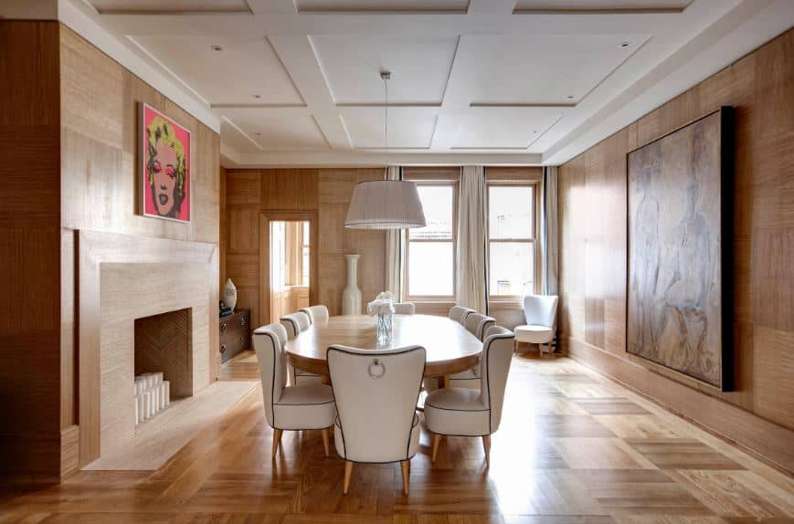 This peculiar dining room has walls with same finish and make as the hardwood flooring with a subtle checkered pattern to it. This complements the large wooden table that can sit eight people on its white leather wing back chairs that match the ceiling.
