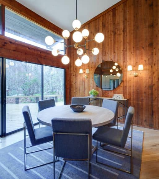The white shed ceiling is contrasted by the wooden walls that are adorned with a wall-mounted round mirror above the console table and flanked by wall lamps that matches with the chandelier over the light gray dining table paired with blue cushioned modern chairs.