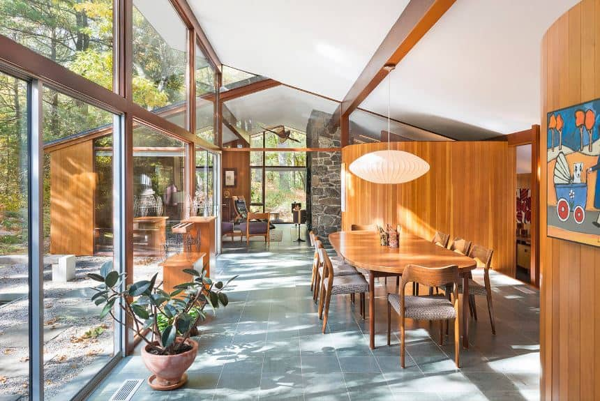 This dining room has an abundance of natural lights coming in from the glass walls on one side that brightens up the white shed ceiling and wooden walls that match with the wooden elliptical table and its wooden chairs over a gray flooring.