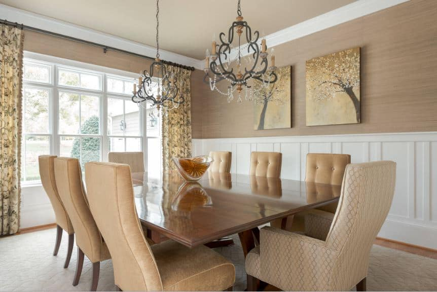 The brown wallpaper of the upper walls are adorned with a couple of artworks of trees that oddly fits well with the two small chandeliers hanging over the rectangular wooden dining table paired with cushioned seats that suits the patterned area rug covering most of the hardwood flooring.