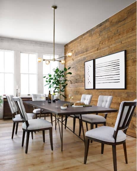 The brown plank wall is decorated with a white minimalist artwork that stands out with its simplicity. This wall is complemented by the light hardwood flooring that makes the black dining table and dining chairs stand out.