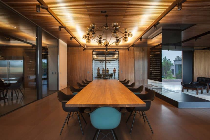 This is a contemporary-style dining room that is dominated the earthy brown hues of the wooden elements seen in the vast ceiling with a slat design, the hardwood flooring and the large wooden dining table that is fit for a conference meeting.