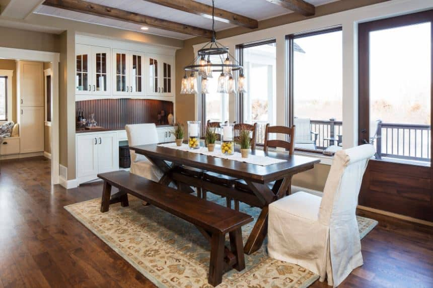 The ceiling is dominated by the dark brown exposed wooden beams that match the dark wooden picnic-style dining table paired with a wooden bench and wooden chairs over a colorful floral area rug that brings a dash of color to the dark hardwood flooring.