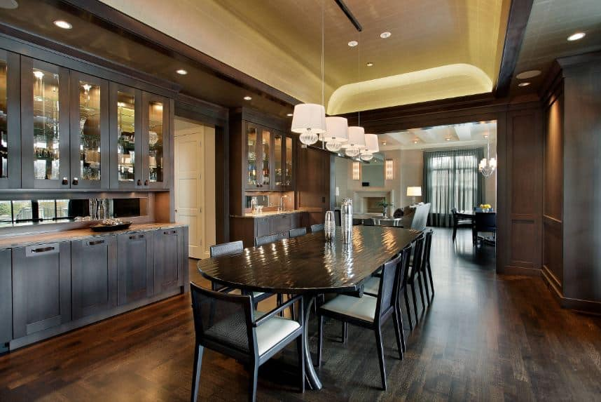 The beige cove ceiling with lights seem to glow against the rest of the dining room that is dominated dark brown elements evident on the dining room cabinets, long dining table, dining chairs and the dark hardwood flooring.