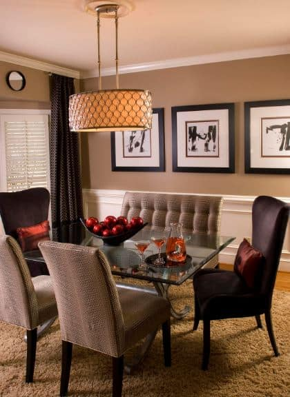 The brown furry area rug over the hardwood flooring is a nice complement for the brown cushioned chairs of the glass-top dining table with a round pendant light hanging over it. It stands out against the brown walls with framed artworks for accent.