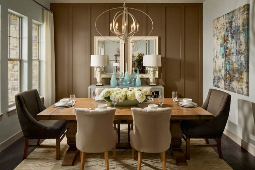 The rectangular wooden dining table has dark brown cushioned chairs on each head that stands out against the beige area rug underneath matching with the rest of the cushioned chairs. This is given a background of a brown wall with mirrors and decors over a light gray dining room cabinet.