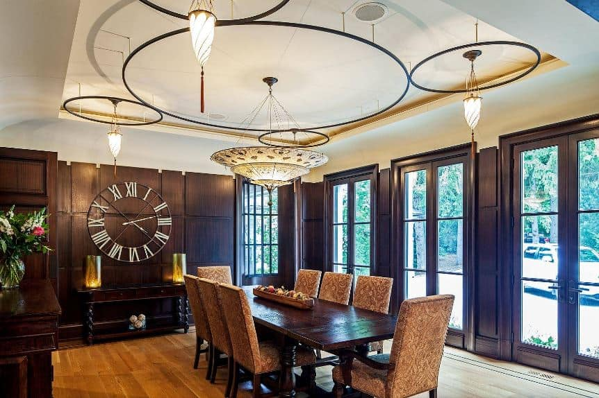 The dark brown wooden finish of the walls of this formal dining room is adorned with a large clock above the wooden console table that matches the dining table and its chic cushioned chairs below a white tray ceiling filled with peculiar decors and lighting.