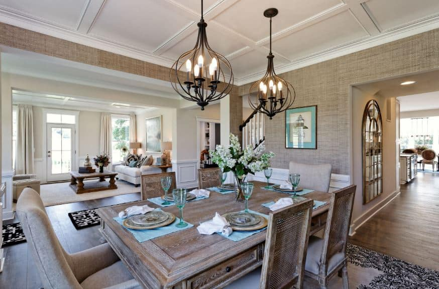 The white coffered ceiling is complemented by the light brown wallpaper of the upper walls that matches with the rectangular wooden table that is paired with rustic wooden chairs with woven wicker backs adorned with a chic patterned area rug.