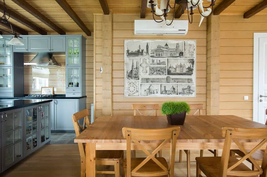 This dining are by the kitchen has the same shiplap finish to its light brown wooden walls and its ceiling with exposed wooden beams. This matches with the wooden dining table surrounded by wooden cross backed chairs over a hardwood flooring of the same hue.