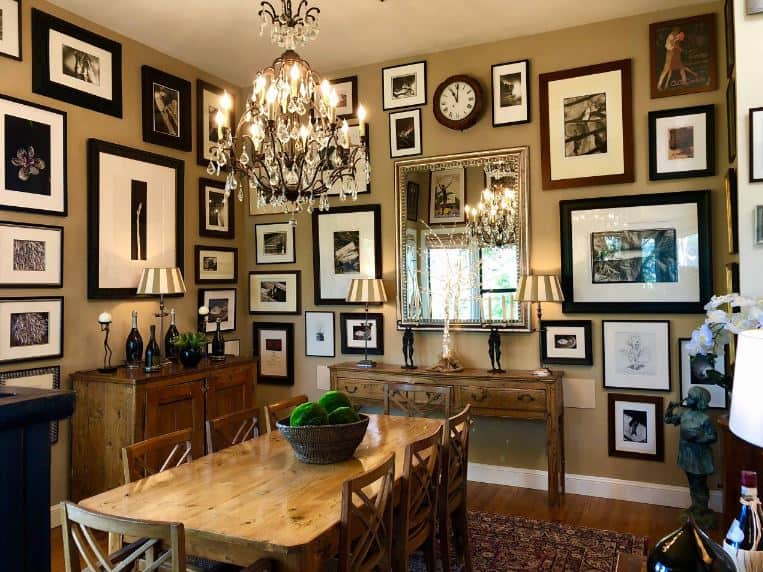 This traditional-style dining room is taken to the next level with its theme of controlled chaos on its brown walls that are almost filled to the brim with framed photos and artworks. This is paired with an ornate crystal chandelier hanging over the wooden dining set.