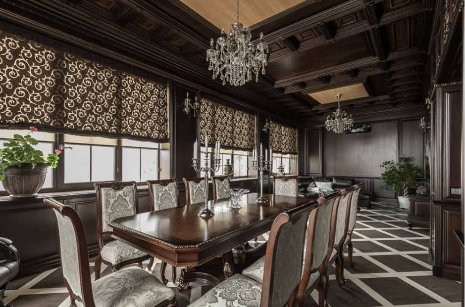 This large formal dining room exudes luxury and elegance with its unique coffered ceiling bearing silvery crystal chandeliers. This aesthetic is mirrored by the dining set that has a large dark brown dining table paired with wooden chairs that have light gray cushions with intricate patterns.
