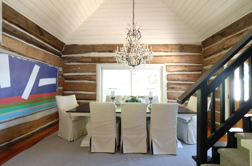 The colorful abstract painting provides a nice dash of color to the walls that are filled with irregular rustic planks to create a unique log cabin feel for the dining room that has a black table and white chairs illuminated by windows.