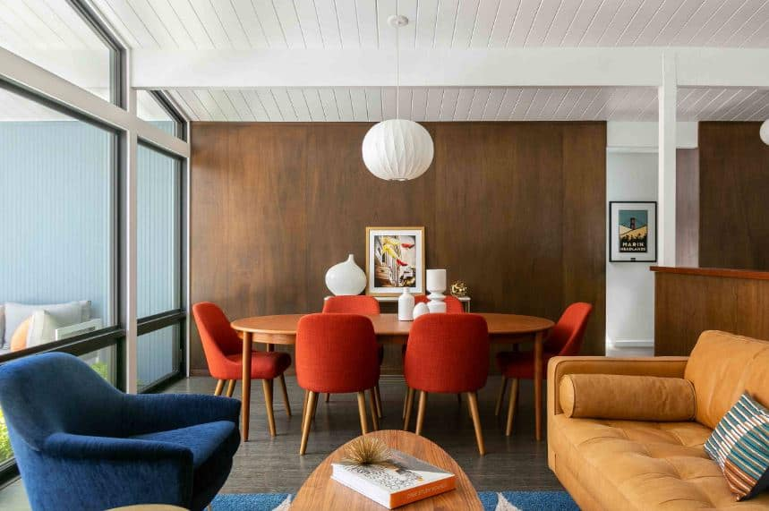 The white shiplap ceiling with an exposed wooden beam matches the design of the white pendant light hanging over the wooden elliptical table that fits well with the orange cushioned sits that stand out against the gray flooring.