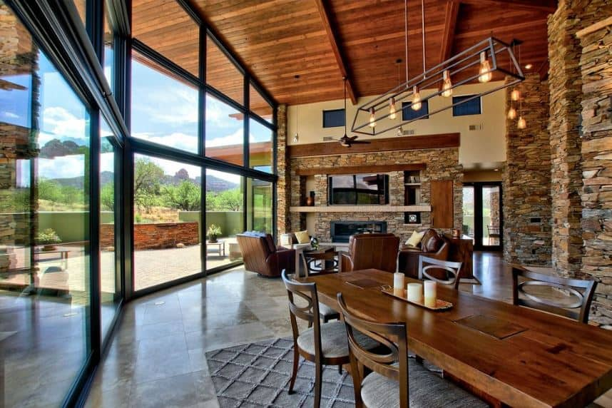 The high wooden ceiling of this great room has wooden exposed beams that is accented with large columns of brown stone on various parts of the great room that has a large glass wall that features an amazing landscape outside that is complemented by the wooden dining table and its wooden chairs.