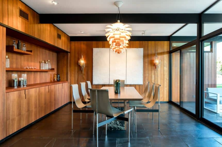 The wall-mounted lamps match the decorative lighting over the wooden table that is paired with modern chairs with unconventional hammock-style design over a black flooring that complements the wooden walls and the large glass doors.
