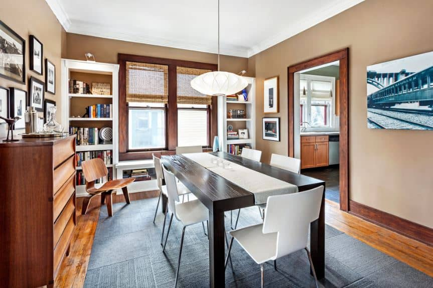 The dark wooden rectangular table contrasts with the white table runner and the modern white wing back chairs that stand out against the dark gray ares rug covering most of the hardwood flooring blending with the molding of the entryway as well as with the frames of the windows.